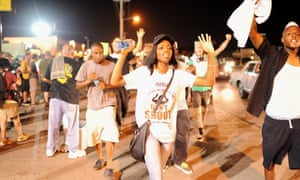 Demonstrators walk and display signs during a peaceful protest on West Florissant Avenue.