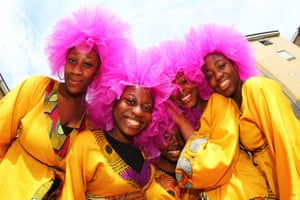 Participants pose for photograph during the first day of the Notting Hill Carnival in London.