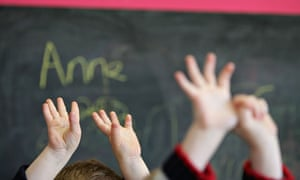 Children hold up their hands in nursery school