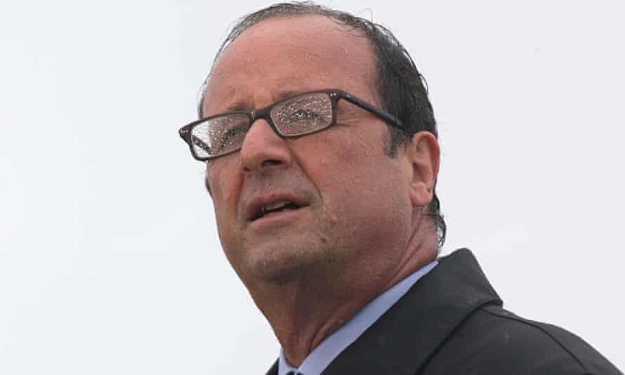 Francois Hollande stands in rain