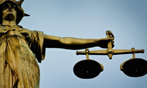 Statute holding scales of justice on top of Old Bailey.