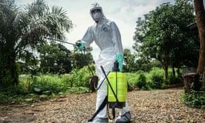 A volunteer sterilises the bodies of Ebola victims ahead of their burials in Kenema, Sierra Leone.