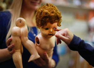 A damaged doll is brought in for repair by a customer.