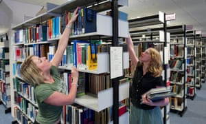 women in library reaching for books