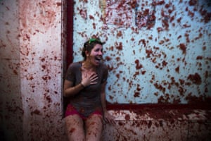 A woman reacts as she takes part in the traditional tomato fight Tomatina in Bunol, Spain