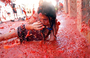 A woman lies in a puddle of tomatoes