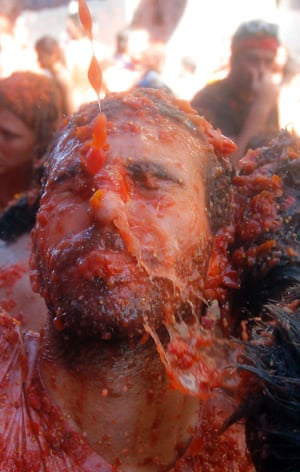 A man reacts as he is hit with tomatoes at La Tomatina