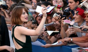 Birdman actor Emma Stone greets autograph hunters on the red carpet. Photograph: Franco Origlia/Getty Images