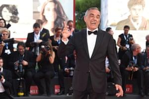 Venice Film Festival director Alberto Barbera winks at the waiting photographers. Photograph: Venturelli/WireImage