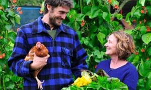 Two farmers in a field: one holds a chicken and the other holds a bunch of flowers...