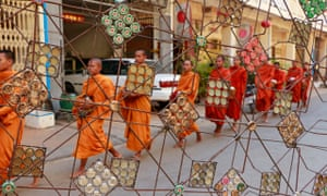 Monks collect morning alms outside Battambang's Make Maek gallery in front of scultpture by Mao Sovi