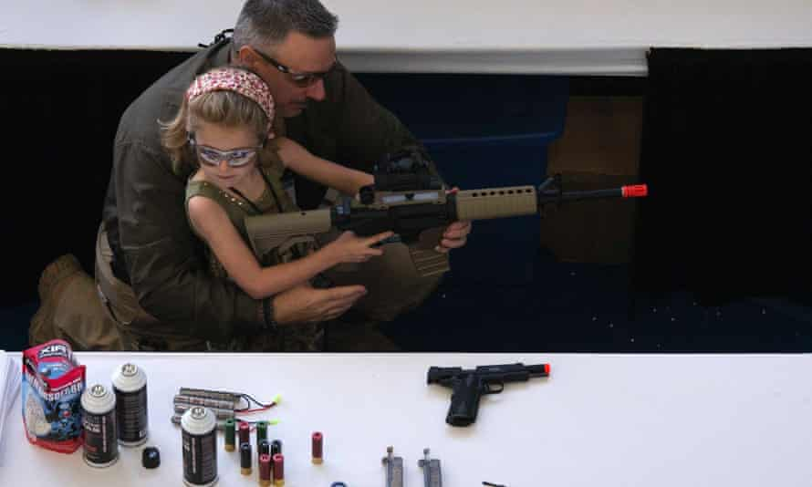 A man shows a girl how to hold an airsoft gun during the NRA Youth Day at the 2013 National Rifle Association's annual meeting in Houston, Texas.
