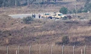 Armed men, reportedly Syrian rebels, standing near the Quneitra border crossing in the Golan Heights