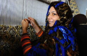 An inmate smiles as she weaves a carpet