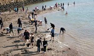 People digging for buried treasure on Folkestone beach