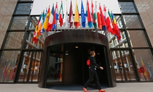 A woman walks past the entrance of the European Council headquarters in Brussels.
