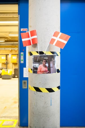 A woman's picture is decorated with Denmark flags inside the factory
