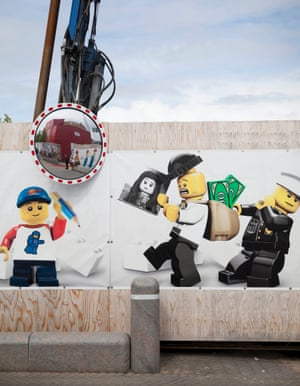 Lego characters adorn the fencing around the site of the new Lego House