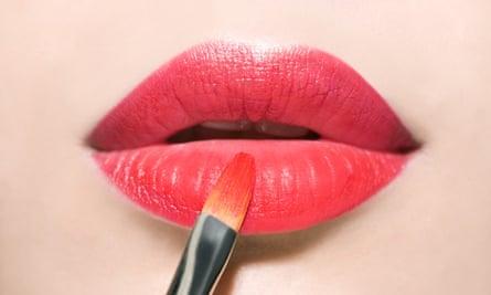 woman applying lipstick to lips
