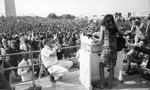 Baez performs onstage for the crowd gathered on the Mall during the Civil Rights March on Washington, D.C., August 29, 1963