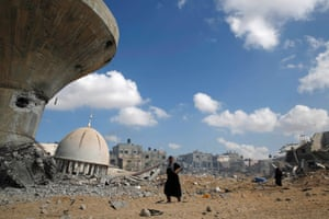 A Palestinian woman walks past a mosque damaged by Israeli strikes in the southern Gaza Strip