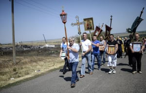 A religious ceremony passes near the crash site of the Malaysia Airlines Flight MH17 near Hrabove