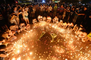 People light candles and pray for victims of a factory blast in Kunshan