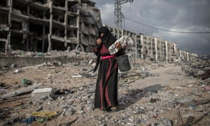 An elderly Palestinian woman walks through ruins in Gaza