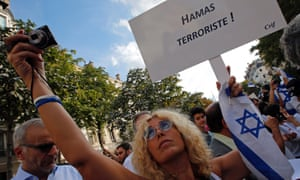 """A woman holds an Israeli flag and a placard reading """"Hamas Terrorist"""" during a gathering in front of the Israeli Embassy in Paris, France, Thursday, July 31, 2014."""
