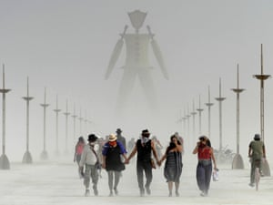 Burning Man participants walk through the dust on the Black Rock Desert of Gerlach.