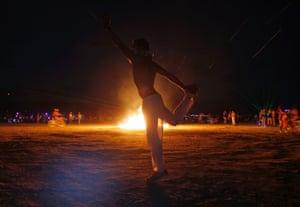 Omri Cohen dances around a burning art installation.