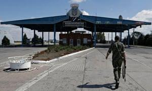 A Pro-Russia rebel walks at the Novoazovsk border crossing point, in eastern Ukraine.