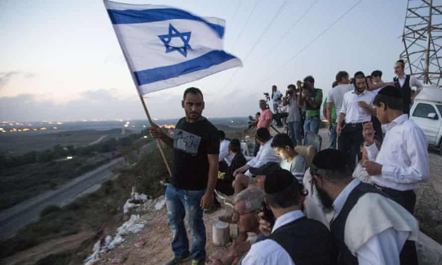 Israelis, mostly residents of the southern Israeli city of Sderot, stand with an Israeli flag on a hill overlooking the Gaza Strip, on July 20, to watch the fighting between the Israeli army and Palestinian militants.