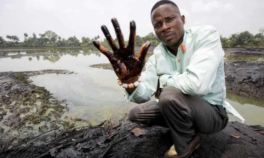 Plaintiff Nigerian farmer Eric Dooh showing his hand covered with oil from a creek near Goi, Ogoniland, Nigeria.