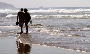 A couple walks through the surf together