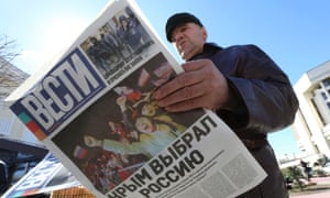 "A man reads a free newspaper with the headline ""Crimea chooses Russia"" on a street in Simferopol in March."