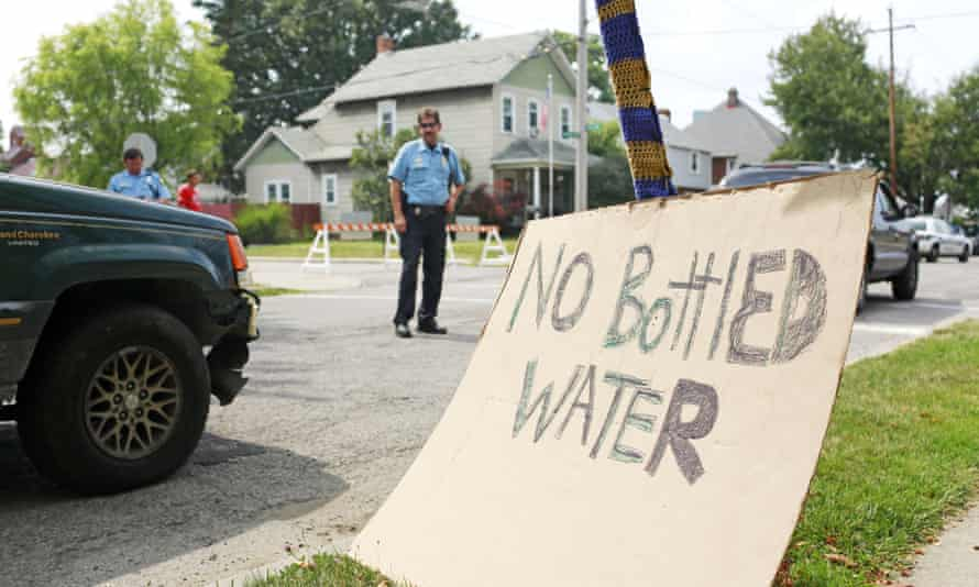 Toledo police officers direct traffic near a water distribution point at Waite High School in Toledo, Ohio. bottled water