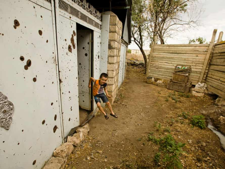 Ibrahim Aliev, 7, plays near the gates to his family home in the village of Chiragli located near the line of contact. Recent days have seen a sharp escalation in fighting between Azerbaijan and Armenia. (AP Photo/ Abbas Atilay )