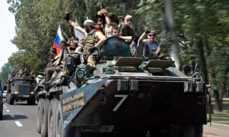 Pro-Russia rebels ride on top of an armoured personnel carrier near Donetsk