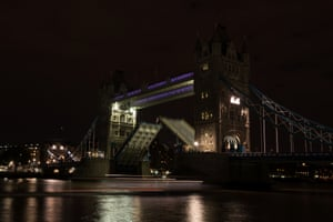 Tower Bridge in London is seen with lights switched off as the bridge lifts for a passing boat