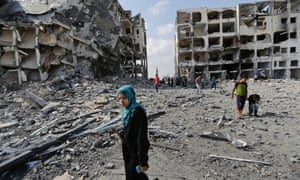 Palestinians inspects damages of the Nada Towers at a residential neighborhood, in the town of Beit Lahiya, northern Gaza Strip, Tuesday, Aug. 5, 2014.