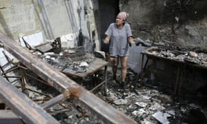 A woman removes debris from a cafe destroyed during fighting between Ukrainian forces and pro-Russian militants in Slavyansk, in the Donetsk region, on 5 August, 2014.