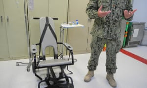 A US naval medic explains the feeding chair at  Guantánamo Bay, Cuba. guantanamo