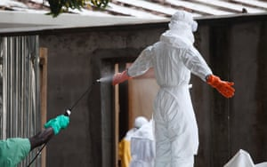 A Liberian nurse in protective clothing is sprayed with disinfectant after preparing bodies of victims of Ebola for burial in the isolation unit of the ELWA Hospital in Monrovia, Liberia.