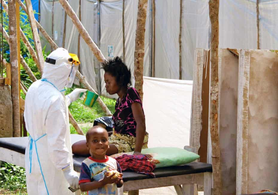 A health worker, wearing personal protection gear, offers water to a woman with Ebola virus disease (EVD), at a treatment centre for infected persons in Kenema Government Hospital, in Kenema, Eastern Province, Sierra Leone in this August, 2014 handout photo provided by UNICEF August 6, 2014.
