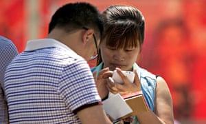 People using their smartphone in Tiananmen Square, Beijing