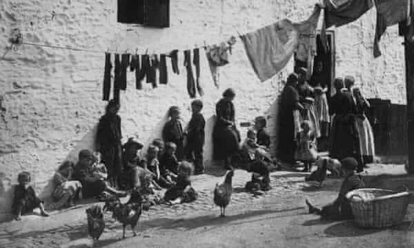 Children sitting under a washing line hanging across a courtyard in a slum area of London in 1889