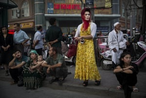 Uighurs wait at a bus stop. Nearly 100 people have been killed in unrest in the tense Xinjiang province in the last week of July.