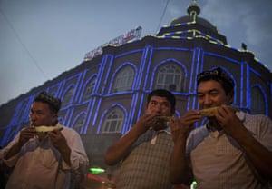 Uighur men eat watermelon as they break their Ramadan fast at a market.