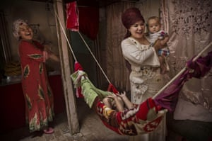 Uighur women care for their children at home.